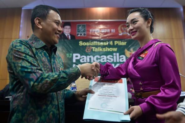 Ketua Fraksi Partai Kebangkitan Bangsa (PKB) MPR Abdul Karding (kiri) menyerahkan piagam kepada Zaskia Gotik disela-sela Sosialisasi 4 Pilar di Komplek Parlemen Senayan, Jakarta,